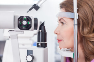 Middle aged woman is looking into eye test equipment with concentration. She is sitting in profile in oculist lab